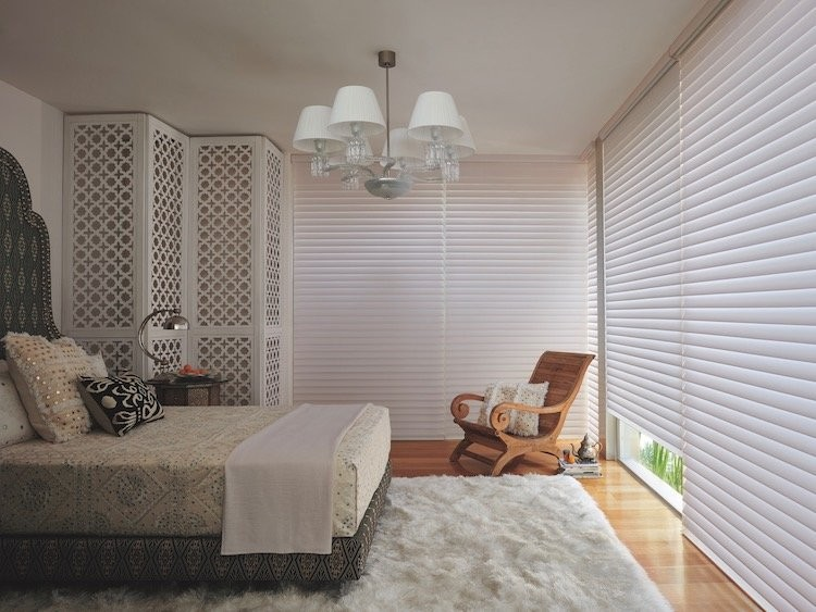 A bedroom with a variety of white textures and patterns